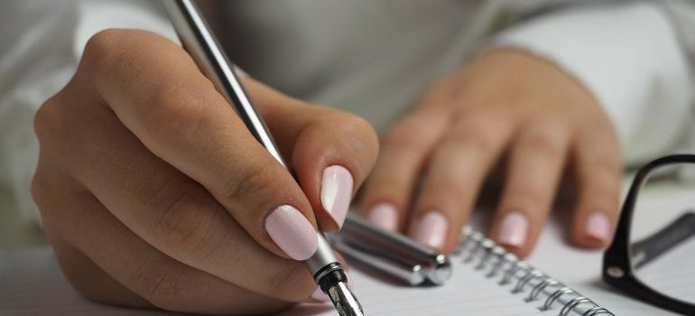 A woman writing in a notebook.
