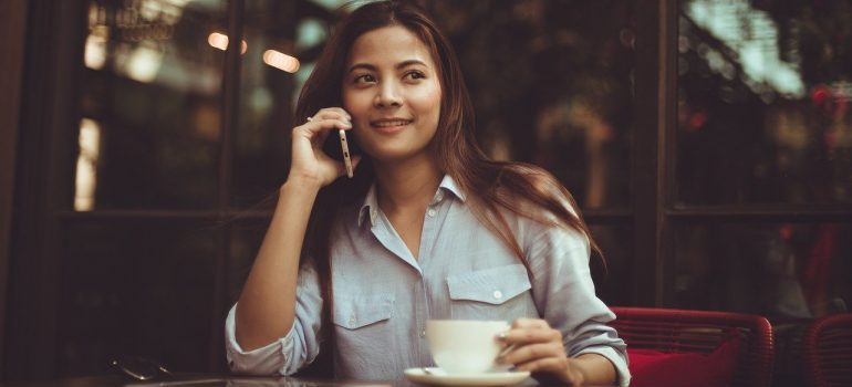 A woman in a coffee shop making a call, contacting moving companies Amherst NY.