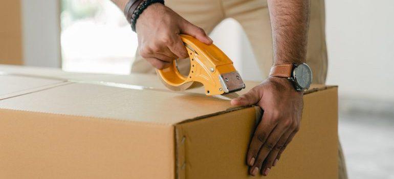 A man taping a cardboard box.