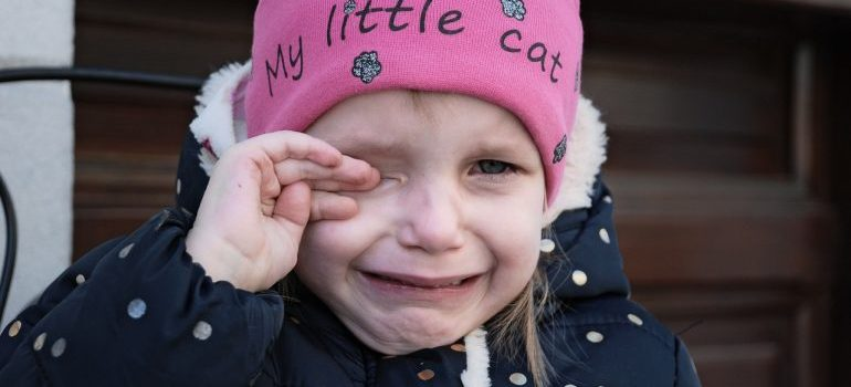 A child with a pink hat, crying.