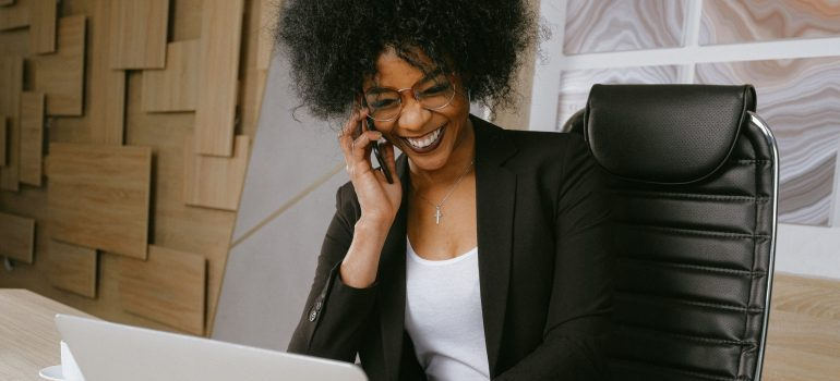 A woman talking on the phone to set deadlines for an office move and smiling.