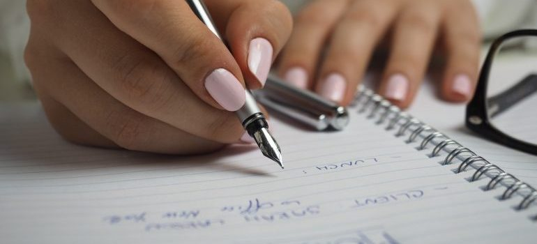 A woman preparing for a local move by writing down reminders.