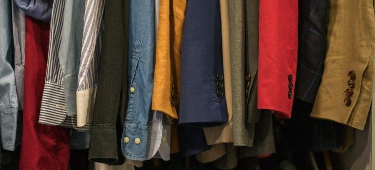 An assortment of different shirts in a closet.
