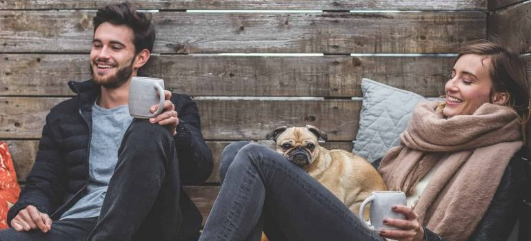 Two people and a pug talking with coffee mugs