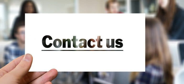 A person holding a piece of paper with the words contact us on it.