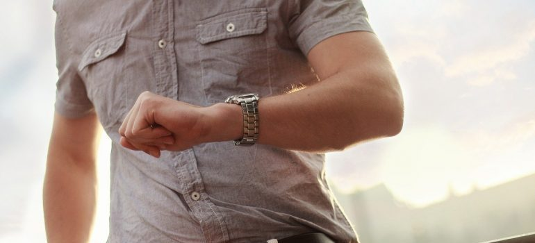 A man looking at a wrist watch.