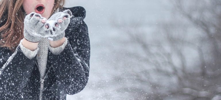 A woman in a winter jacket blowing snow out of her hands.
