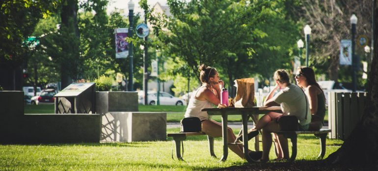 Women sitting on benches in a park showing you how to get to know Jamestown after your move