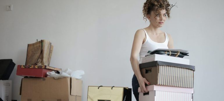 Woman carrying cardboard boxes in an apartment