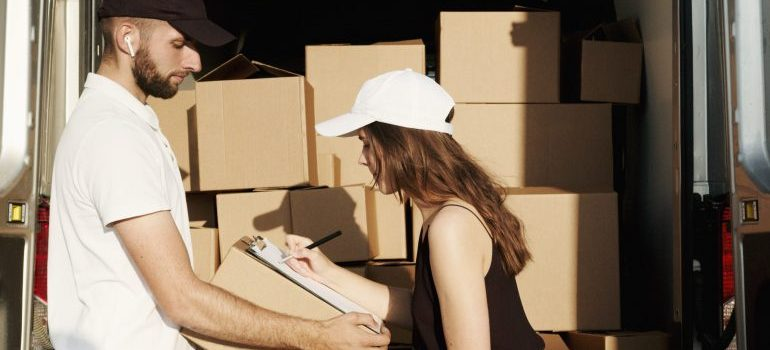 A woman signing a contract she read as an an example of to avoid misunderstandings with your moving company