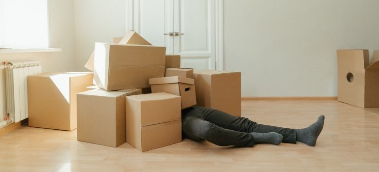 A man underneath a huge pile of boxes he will need to pack fragile items for relocation