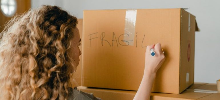 A woman labeling a moving box as fragile