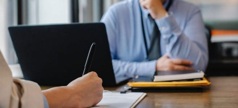 Person signing a contract in an office